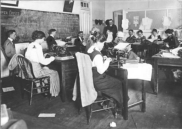 School of Journalism, women and men students in typing class and Professor Enoch