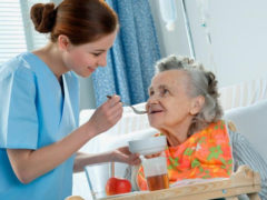 Nurse feeding a resident at a nursing home