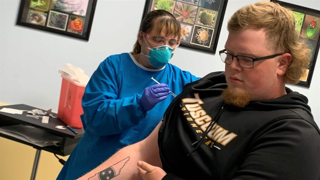 Colton James Edwards, a student at Tusculum University in Tusculum, Tennessee, receives a COVID-19 shot at Plateau Pediatrics in Crossville.