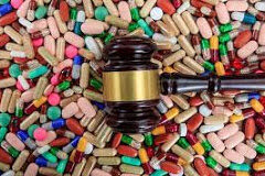 A gavel laying on top of a pile of pills