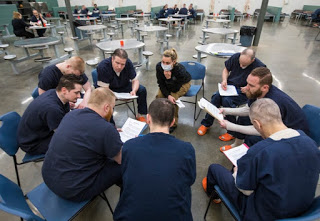 Inmates in the drug treatment program sitting in chairs in a circle, each looking at a notebook