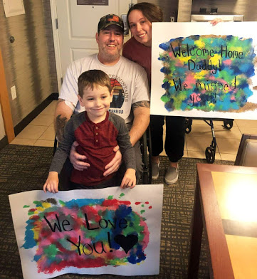 """A white man in his 40s in a wheelchair. His wife is crouching next to him and holding a sign that says """"Welcome Home Daddy! We missed you!"""" A young boy is standing in front of the man, holding a sign that says """"We Love You!"""""""