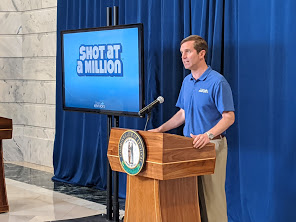 Andy Beshear standing at a lectern